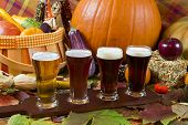 stock photo of porter  - oktoberfest beer flight of four samples with fall seasonal decoration - JPG
