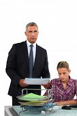 Businessman giving his overworked assistant more work