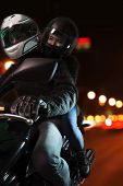 Young couple riding a motorcycle through the city streets at night