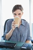Businesswoman drinking of disposable cup sitting at her desk looking at camera