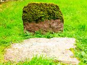 stock photo of tombstone  - Aged gravestone tombstone with moss green grass in an ancient church graveyard - JPG