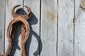 picture of yesteryear  - A rusty old horseshoe and farrier trim tool hang on a weathered barn wall a memory of days gone by - JPG