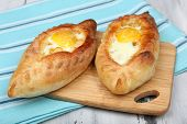 Ajarian khachapuri on wooden table close up