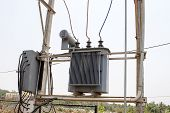 small transformer fixed to a double pole structure on a light blue sky background
