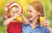 Family Mother And Baby Daughter Drinking Orange Juice In The Summer