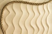 Nautical Background Of Wavy Sand With A Rope