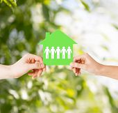 real estate and family home concept - isolated closeup picture of male and female hands holding gree