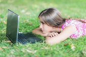 Teenage girl laying in the grass looking at  her laptop computer