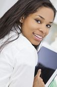 Beautiful happy young African American woman or girl smiling and using a tablet computer
