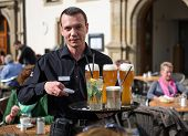 STUTTGART, GERMANY - APRIL 01, 2014: Waiter with glasses of beer and alcoholic drinks on his tray. Old Chancellery(Alte Kanzlei) square