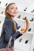 Portrait of woman keeping brown leather shoe in shopping center against the showcase with pumps