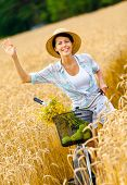 Girl pedals bicycle and waves hand in rye field. Concept of rural lifestyle and sport