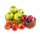 Green and red apples in a wicker baskets, isolated on white background.