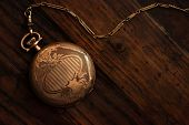 Antique pocket watch on rustic dark wood background with copy space.  Low key still life with direct
