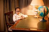 Girl In Eyeglasses Sitting Behind Table At Cabinet