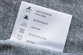 stock photo of knitwear  - Label with washing instructions on gray knitted fabric - JPG