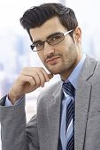 Close-up portrait of handsome young businessman in glasses, smiling.