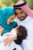 happy middle eastern couple and baby boy outdoors