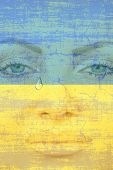 Young Pretty Womans Face With Tear On Ukranian Flag Background.