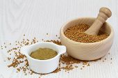 pic of mustard seeds  - Mustard seeds in wooden mortar and mustard in white bowl with copy space - JPG