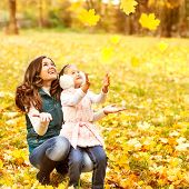 Mother And Daughter Having Fun In The Autumn Park Among The Falling Leaves.