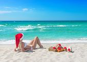Beautiful Blonde Woman In Bikini, Red Christmas Hat And Gift Boxes on sea beach, new year concept