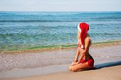 Beautiful Woman In Santa Hat On The Sea Beach.