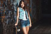 image of skate board  - Beautiful Asian teen girl with skate board. Outdoors, urban lifestyle. ** Note: Soft Focus at 100%, best at smaller sizes - JPG