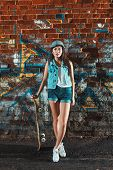 foto of skate board  - Beautiful Asian teen girl with skate board. Outdoors, urban lifestyle.
