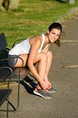 Female Athlete Lacing Sport Shoes Before Running In Park