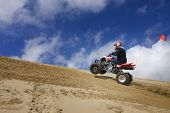 Male Riding Atv Up Sand Dune Hill