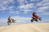 stock photo of four-wheeler  - Two quad riders jumping sand dunes on a sunny day - JPG
