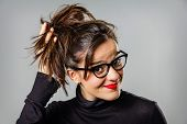 picture of grey-haired  - Portrait of real young girl with glasses and red lips touching her hair bun over a gray background - JPG