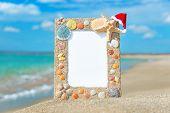 Sea Shells Frame With Christmas Hat Against Sea Beach