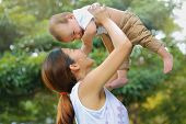 image of kiddie  - Asian family Mother holding her baby was laughing in park - JPG