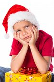 stock photo of sad christmas  - Sad boy with gift box in christmas hat - JPG
