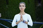 Portrait of pretty woman makes morning yoga meditation outdoors