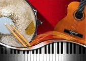 picture of guitar  - Red velvet background with acoustic guitar piano keyboard and metallic old snare drum - JPG