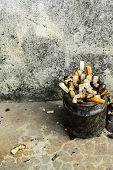Closeup filter cigarette in ashtray glass on floor