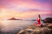 picture of karnataka  - Woman doing meditation in red costume on the stone near the ocean in Gokarna Karnataka India - JPG