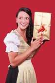 Young woman with dirndl and a great gift in hand