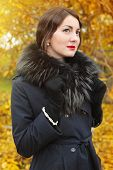 Woman In A Black Coat On Background Of Autumn Tree