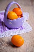 stock photo of kumquat  - Ripe fruit kumquat orange lying on a wooden surface against the background of purple basket - JPG