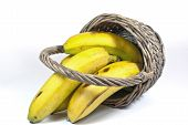Four Yellow Bananas In An Upturned Wicker Basket