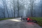 image of crime scene  - A bicycle left alone in the park street at nighttime with the lights on 