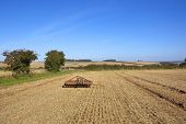 picture of cultivator-harrow  - scenic agricultural landscape in autumn with hawthorn hedgerows and red farm harrows under a blue sky - JPG
