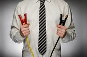 Man with tie holding jumper cables