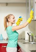 people, housework and housekeeping concept - happy woman in protective gloves cleaning cabinet with rag and cleanser at home kitchen