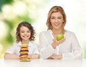 people, healthy lifestyle, family and unhealthy food concept - happy mother and daughter eating different food over green background