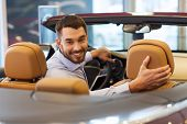 auto business, car sale, consumerism and people concept - happy man sitting in car at auto show or salon